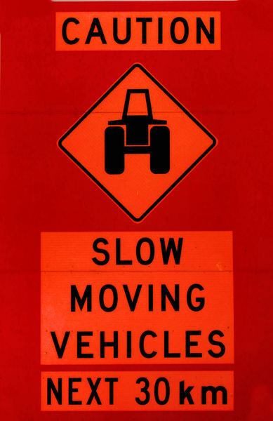 slow and cautious1: tractor caution rural sign