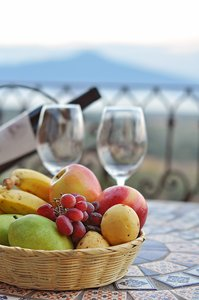 Fruit Basket: Fruit basket on a table, mountain and lake in the background, out of focus
