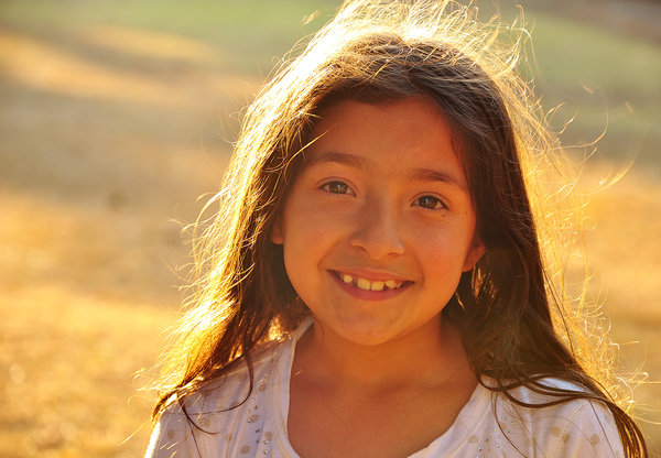 Young girl Smiling at camera: Young girl at the park, smiling at camera, with sunlight shining on hair