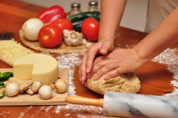 Kneading Pizza dough: Woman kneading whole-wheat Pizza dough on a wooden table, with ingredients in the background