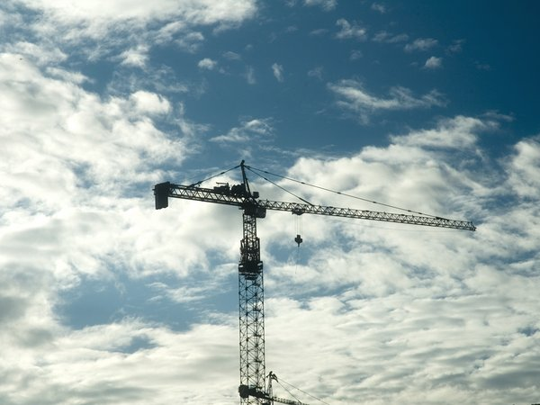 crane: Crane at a construction site, seen against a dark blue clouded sky.