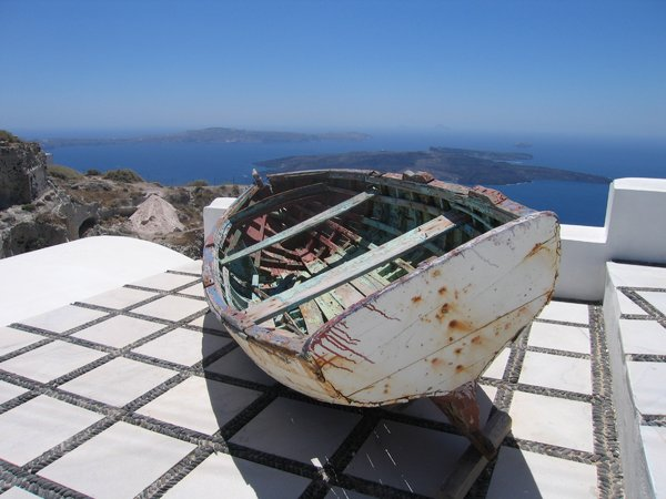 boat on roof: a boat on a roof high above the waterline in Santorini, Greece