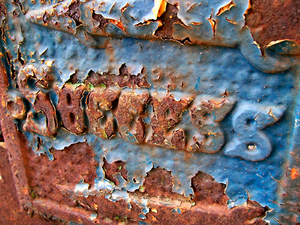 success in rust & paint: The word success on a rusty metal door with peeling paint