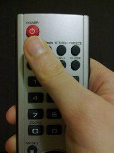 Remote control: A hand holding a remote control for a television.