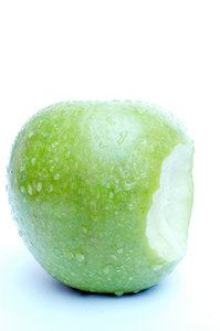 Apple with waterdrops and bite: A fresh green tasteful apple with waterdrops and a bite ...