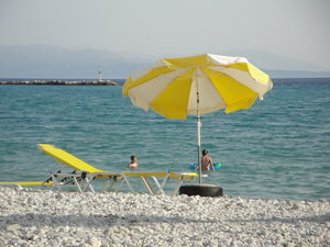 sunny day: beach with pebbels and parasols and a blue sea