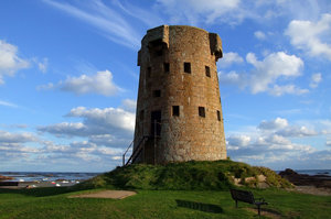 the beach tower: an old tower standing on a beach on the island of jersey, last used in world war 2