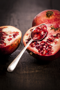 Pomegranate.: Pomegranate fruit on a old wooden table with a silver spoon.
