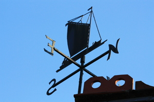 Weather vane: Black metal feature weather vane against a clear blue sky