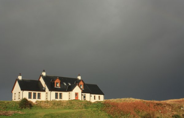 House on a hill: House on a hill against a stormy sky