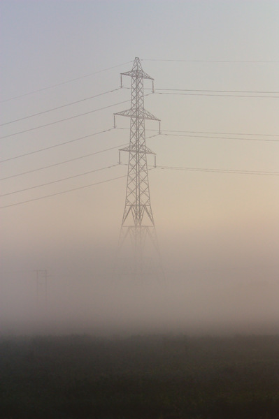 Electricity Pylon in mist: An Electricity Pylon looming through the morning mist