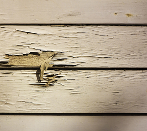 Peeling Paint: Water and sun damage on side boards of house
