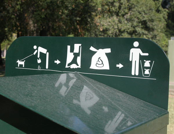 "Pick up after your pooch: Signage on top of a ""dog poop station"" at a public park. It's basically a garbage bin with a plastic bag dispenser attached."