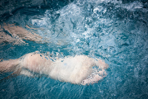 swimming feet: swimmer's feet kicking through water in pool