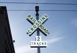 Railroad crossing: A traditional X-shaped railroad crossing sign against a blue sky.