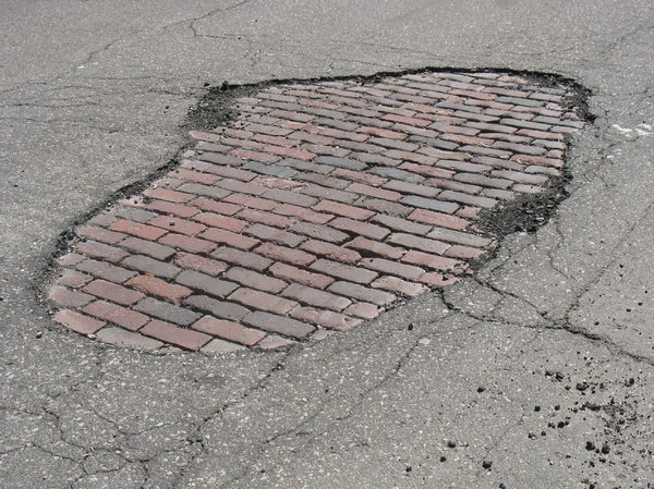 damaged pavement: a damaged patch in the pavement, revealing a brick road underneath.