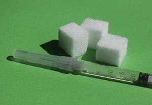 Diabetes: Syringe with insulin and sugar cubes