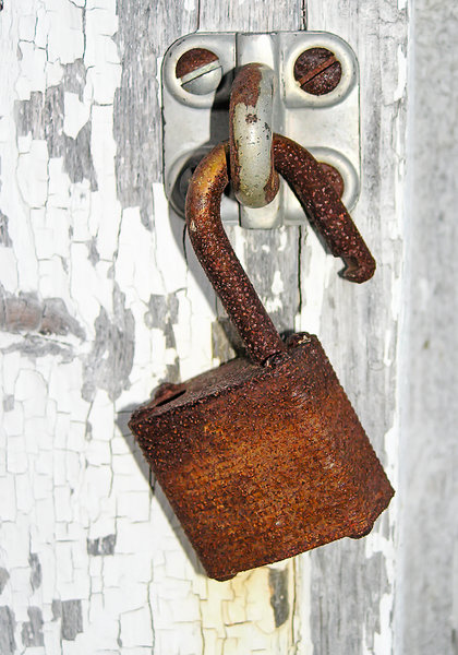 Old Rusted Padlock: A close up of a very old rusted padlock on an old door.