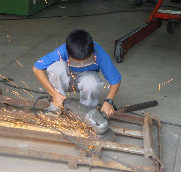 an worker boy: A child learn his job in a workshop.