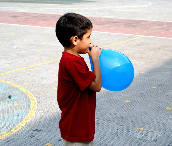 blowing illusions: A child plays seriously with his fragile globe.