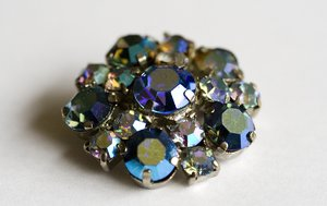 Earring: An antique earring with shiny colored stones.