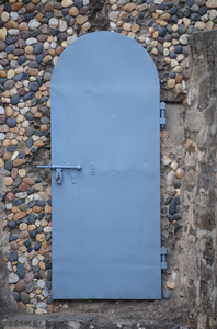Blue door: A blue metal door amongst the stone mosaic walls at the Rock Garden in Chandigarh, India.