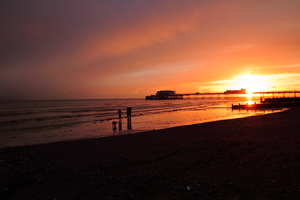 Sunset over a pier: The sun setting over Worthing pier in late November