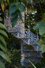 Staircase into the green: White romantic metal staircase going up into the green trees