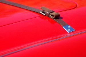 Leather strap on hood: A red classic sportscar with a leather strap to hold the hood/bonnet.