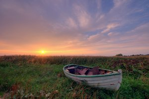 Stranded - HDR: Small dinghy/boat stranded in the grass in full sunset settings. The image is HDR.