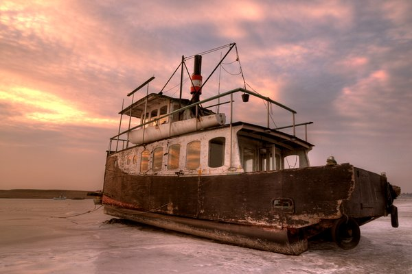 Old ferry in sunset - HDR: Old ferry in sunset, locked in the ice. The picture is HDR.