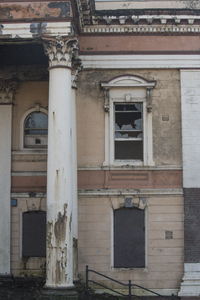 Crumlin Road Courthouse: Vertical exterior view of building with broken and boarded up windows and peeling architectural features of the old  and abandoned Crumlin Road Courthouse in Belfast, Northern Ireland