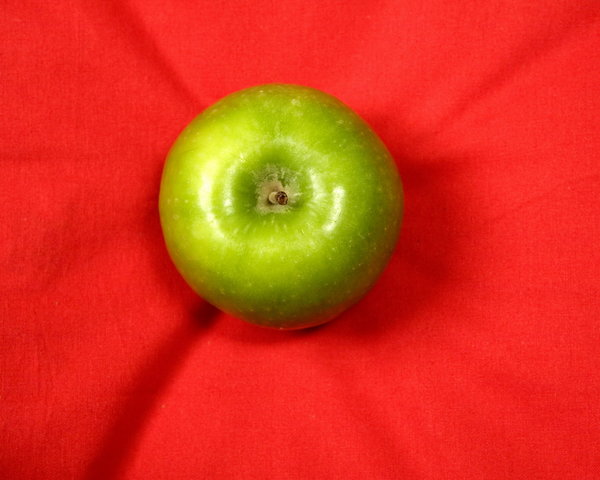 green apple: green apple on the red background