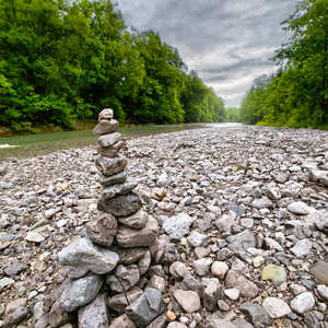Pebble Pyramid at Mountain Riv: Pebbles built to a Pyramid, at a River in the Bavarian Mountains. Rain Weather, cloudy Sky.