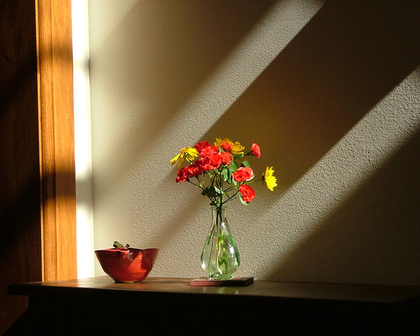vase of flowers in shadows and: A vase of red and yellow flowers in rays of sun and shadow on a wooden table next to a ceramic bowl. Interesting how it looks as if a shadow is cast upon the flowers but they glow in the light anyway.