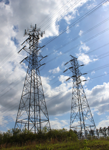 transmission towers: two giant transmission towers stand in front of sky.