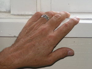hand on window sill: man's hand with ring on wooden window sill