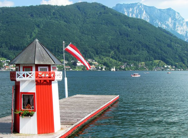 At the lake again: lake traunsee in upper austria. funny little tower on the landing stage, austrian flag waving in the wind.