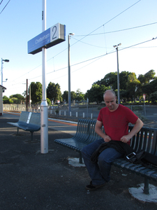 A man at a train station: A young man smiles at a camera while waits for his train