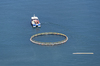 Boat towing a fish pen: A motorboat towing a fish pen into position off the coast of southern Italy.
