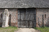 Old barn: An old disused brick, cobble and thatch barn with archers' slots in Norfolk, England.