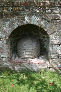 Traditional beehive: A skep (an old traditional beehive made of woven fibre) in its purpose-built recess in the garden wall of a manor house in England.