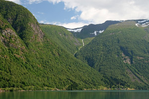 Green hills: Forested hills surrounding a tiny fjord-side village in Norway.