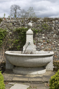 Ornamental water trough: An old ornamental stone water trough in a walled garden in England in spring.