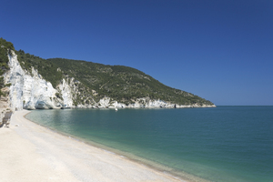 Beautiful beach: A sand and shingle beach in front of chalk cliffs in the Gargano region, Puglia, Italy.