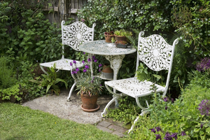 Garden table and chairs: A table and chairs in a cottage garden in West Sussex, England.