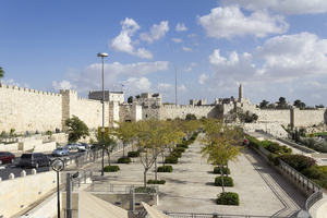 Jerusalem old and new: Part of the ancient wall of the Old City of Jerusalem, with a modern road and promenade adjacent.