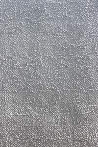 Wall texture: Plastered wall with applied surface texture, photographed in oblique light.