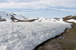 Thick snow: Melting snow on mountains on a high plateau in Norway in July.