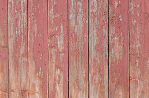 Grungy boards texture: Wooden boards with peeling red paint on the side of a traditional house in Norway.